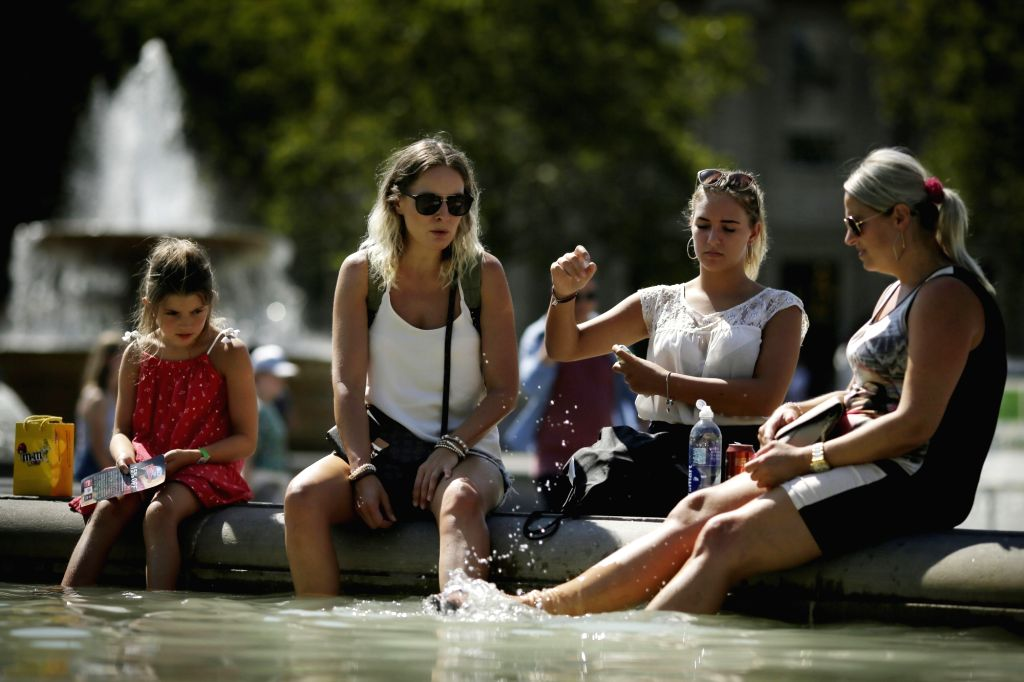 LONDON, Aug. 3, 2018 - People cool off at a fountain at Trafalgar Square in London, Britain, on Aug. 3, 2018. Britain is currently experiencing high temperatures as a heatwave continues across Europe.