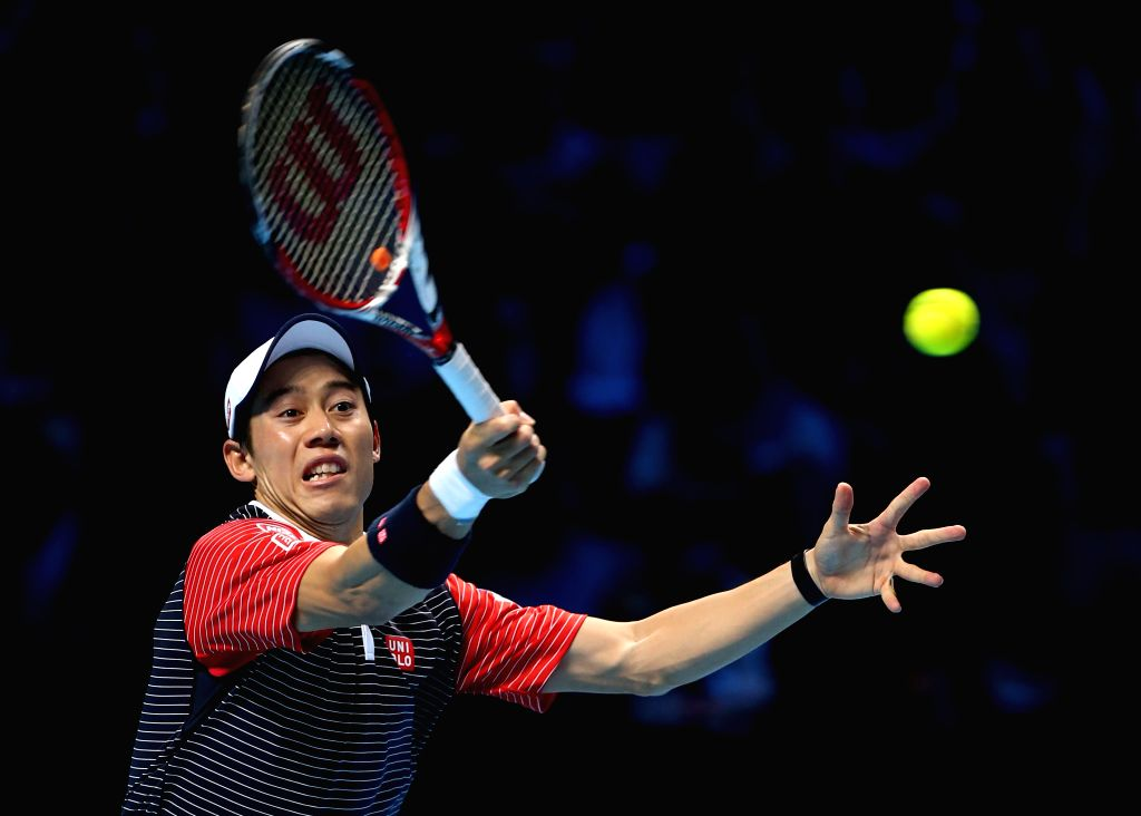 London (Britain): Kei Nishikori of Japan returns the ball during the ATP World Tour Finals Group match against Roger Federer of Switzerland in London, Britain, on Nov. 11, 2014. Kei Nishikori lost ...