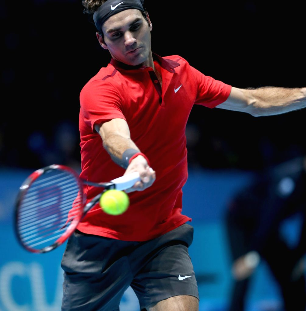 London (Britain): Roger Federer of Switzerland returns the ball during the ATP World Tour Finals Group match against Kei Nishikori of Japan in London, Britain, on Nov. 11, 2014. Federer won 2-0. ...