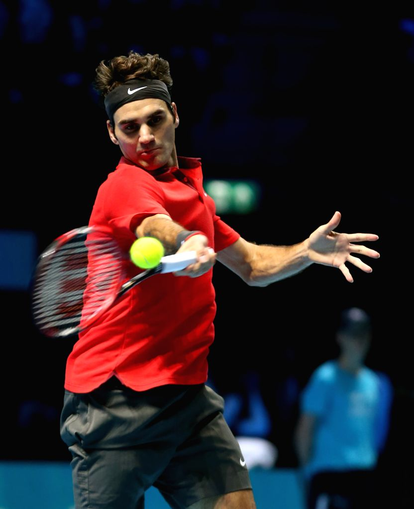 London (Britain):Roger Federer of Switzerland hits a return during the ATP World Tour Finals Group B match against Milos Raonic of Canada in London, Britain, on Nov. 9, 2014. Federer defeated Raonic .