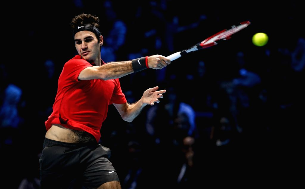 London (Britain): Roger Federer of Switzerland hits a return during the ATP World Tour Finals round robin match against Andy Murray of Britain in London, Britain, on Nov. 13, 2014. Federer defeated ..