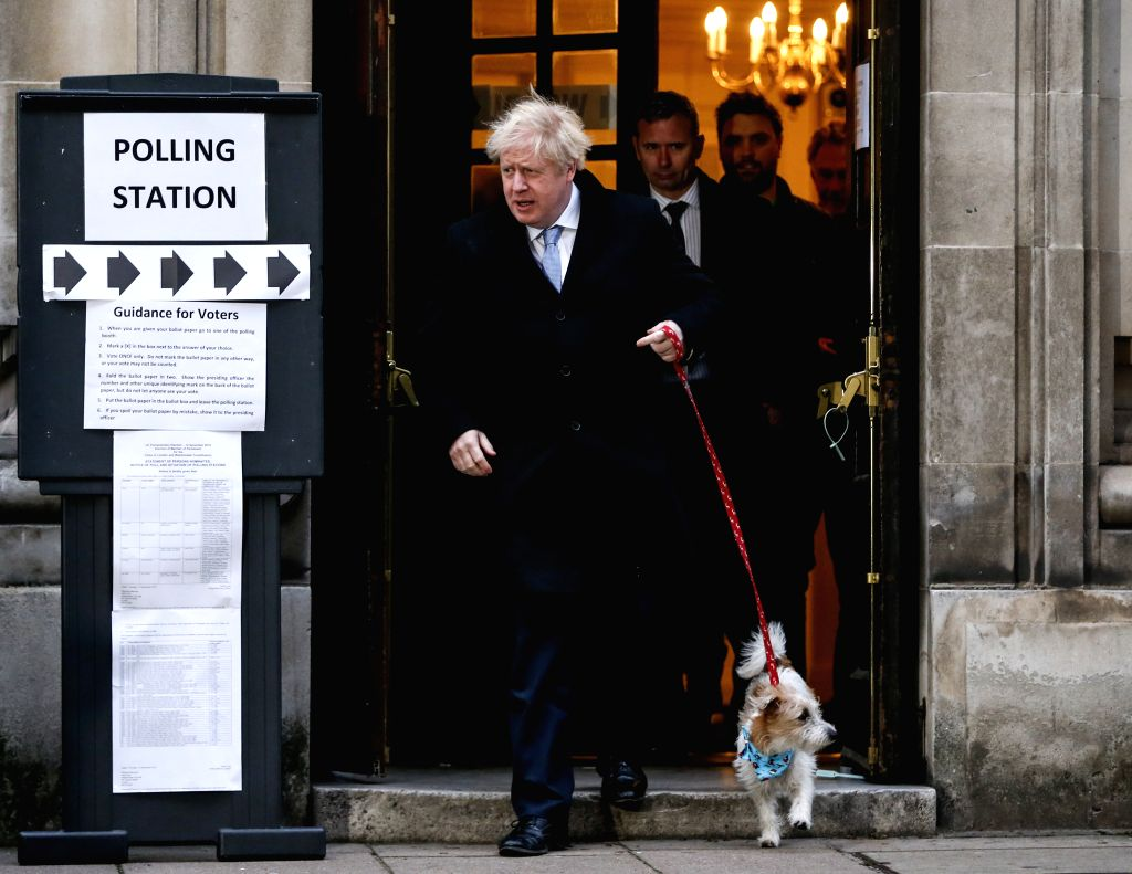 LONDON, Dec. 12, 2019 - British Prime Minister and Conservative Party leader Boris Johnson leaves a polling station with his dog after casting his vote for the general election in London, Britain on ...