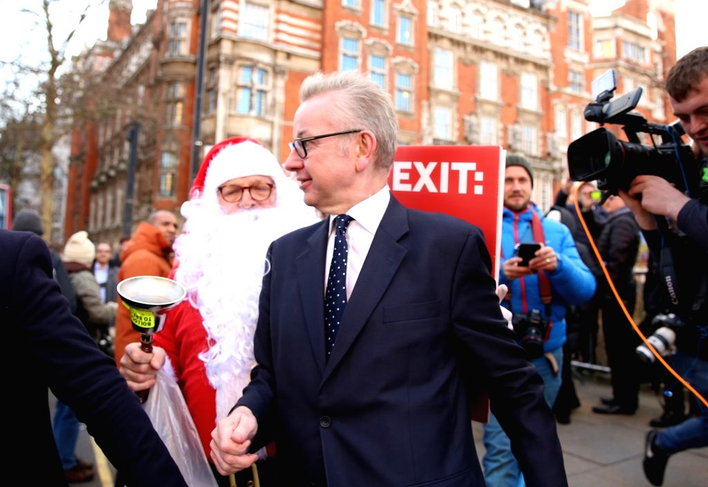 LONDON, Dec. 13, 2018 - British Secretary of State for Environment, Food and Rural Affairs Michael Gove is followed by an anti-Brexit supporter on his way into the Houses of Parliament in London, ... - Theresa May