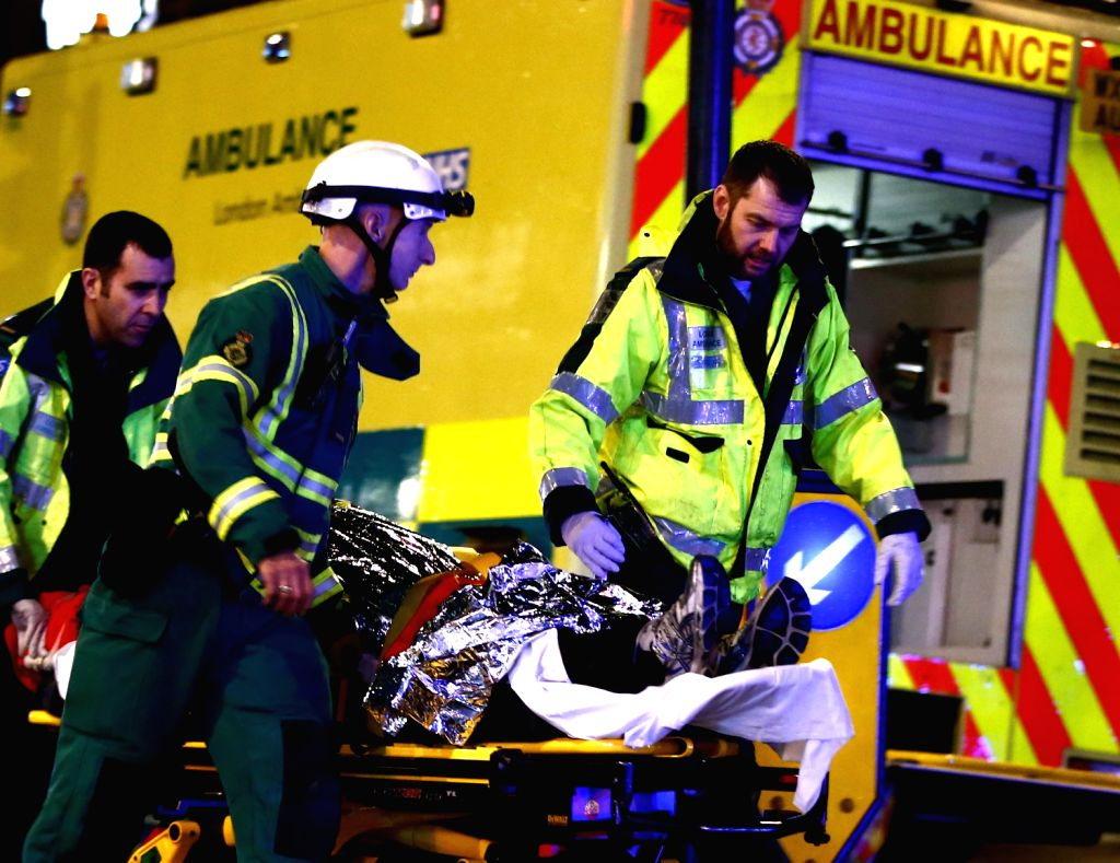 An injured person is taken towards a waiting ambulance on a stretcher following a roof collapse at a theatre in central London on Dec. 19, 2013. Some 88 people .