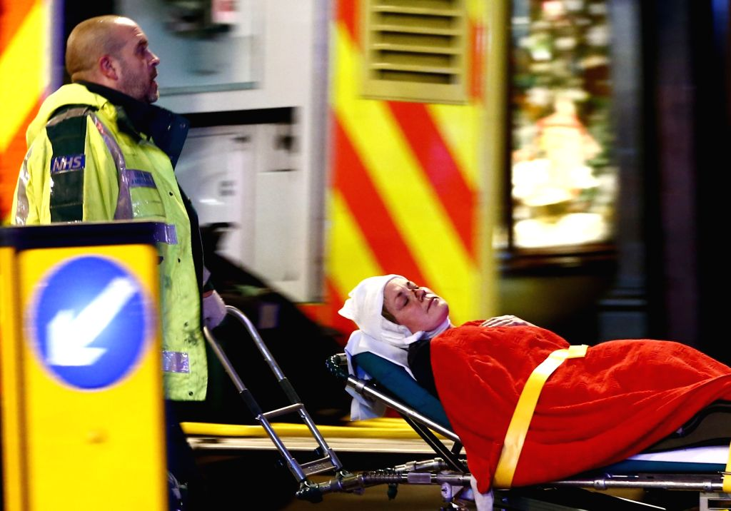 An injured woman is taken towards a waiting ambulance on a stretcher following a roof collapse at Apollo Theatre in Central London on Dec. 19, 2013. Some 88 ...