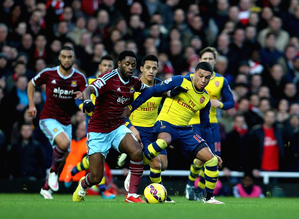 Alex Oxlade-Chamberlain (R, Front) of Arsenal vies with Alex Song of West Ham United during the Barclays Premier League match between West Ham United and Arsenal at .