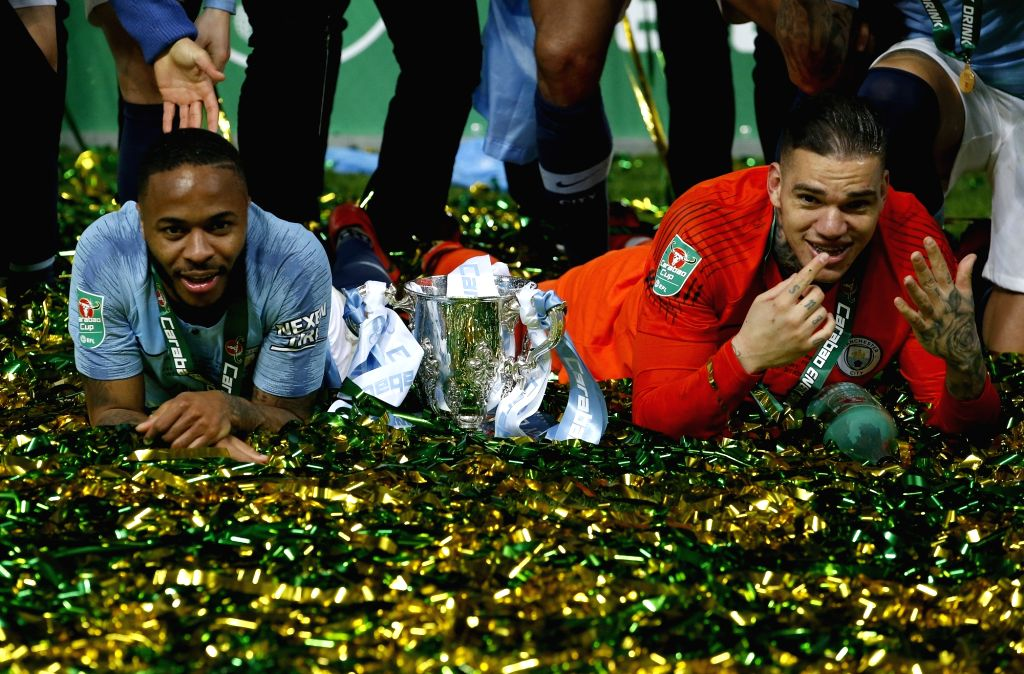 LONDON, Feb. 25, 2019 - Manchester City's Raheem Sterling (L) and goalkeeper Ederson celebrate on the ground with the Carabao Cup after the Carabao Cup Final match between Chelsea and Manchester City ...