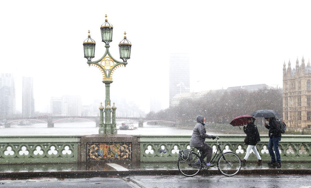 LONDON, Jan. 13, 2017 - People walk through the Westminster Bridge in snow in central London, Britain, on Jan. 13, 2017.