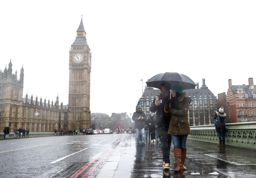 """LONDON, Jan. 13, 2017 - Tourists walk past the """"Big Ben"""" in snow in central London, Britain, on Jan. 13, 2017."""