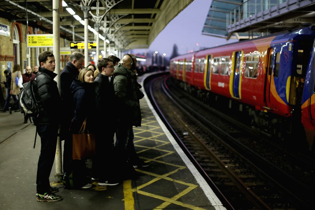 LONDON, Jan. 8, 2018 (Xinhua) -- Commuters wait on a platform at Clapham Junction Station as Rail, Maritime and Transport (RMT) union members hold placards at Waterloo Station as Northern, Merseyrail, South Western Railway and Greater Anglia workers