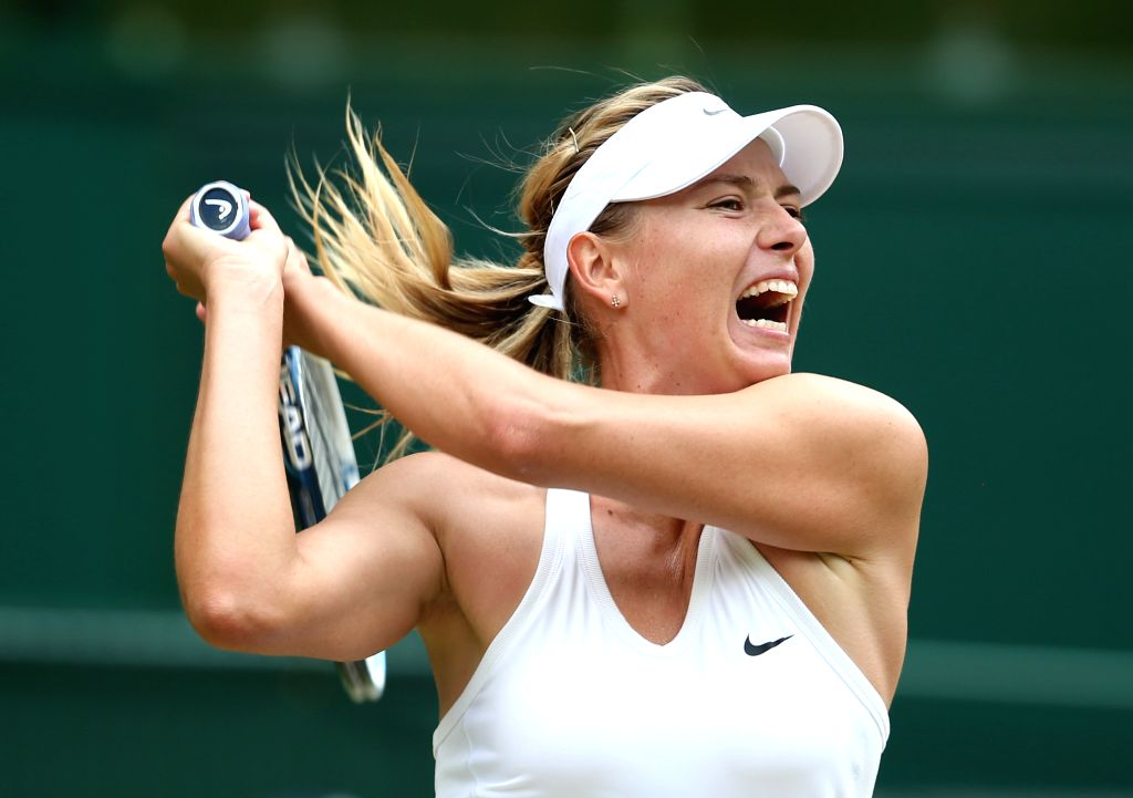 Russia's Maria Sharapova returns a shot during the women's singles fourth round match against Germany's Angelique Kerber at the 2014 Wimbledon Championships in ...