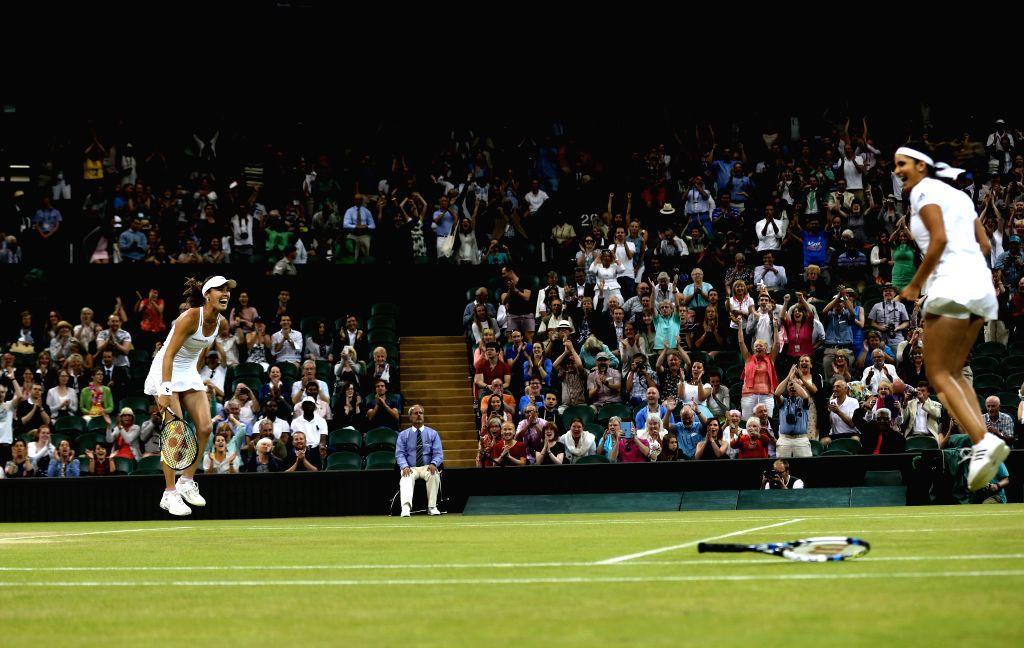 LONDON :JULY 12, 2015 Martina Hingis(L) of Switzerland and Sania Mirza of India celebrate after winning the women's doubles final against Ekaterina Makarova/Elena Vesnina of Russia at the ... - Martina Hingis and Sania Mirza