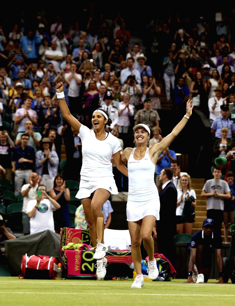 LONDON :JULY 12, 2015 Martina Hingis(L) of Switzerland and Sania Mirza of India pose with the trophy in the royal box during the awarding ceremony for the women's doubles final against ... - Martina Hingis and Sania Mirza