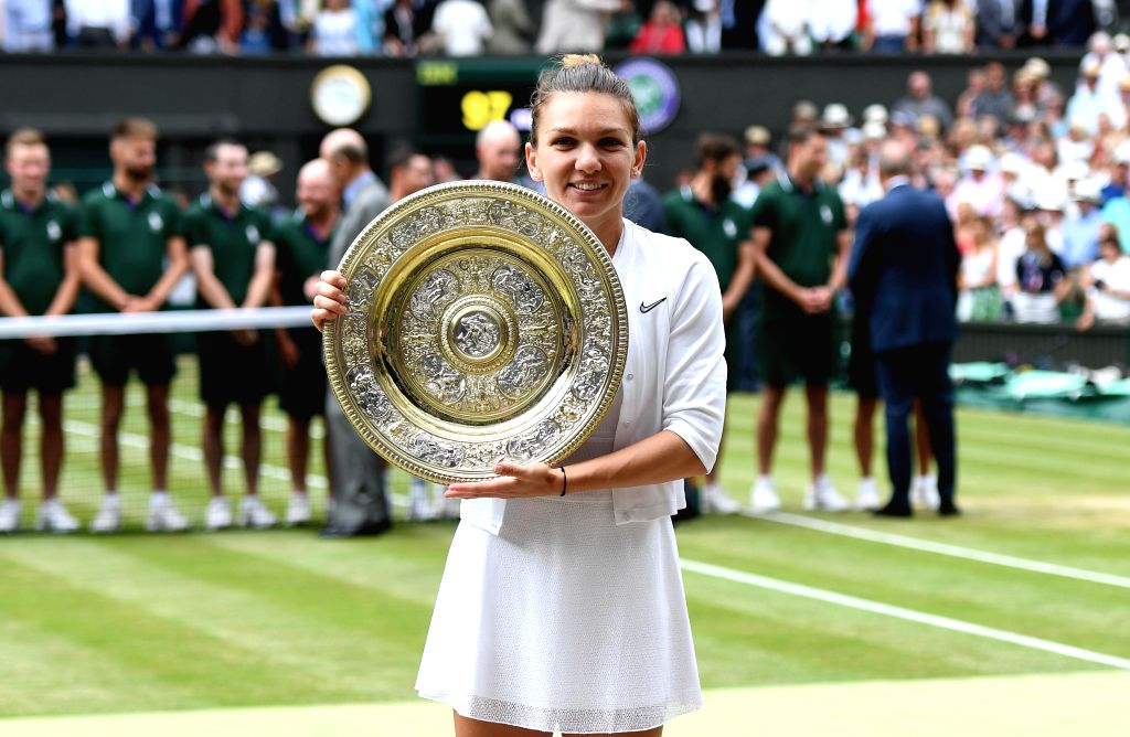 LONDON, July 13, 2019 (Xinhua) -- Simona Halep of Romania holds the trophy after winning the women's singles final match between Serena Williams of the United States and Simona Halep of Romania at the 2019 Wimbledon Tennis Championships in London, Br