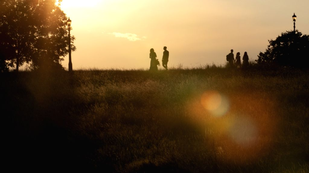 LONDON, July 27, 2018 - People are silhouetted in sunset on the top of a hill in London, Britain on July 26, 2018. Temperatures in the coming days could break all-time UK records, with the mercury ...