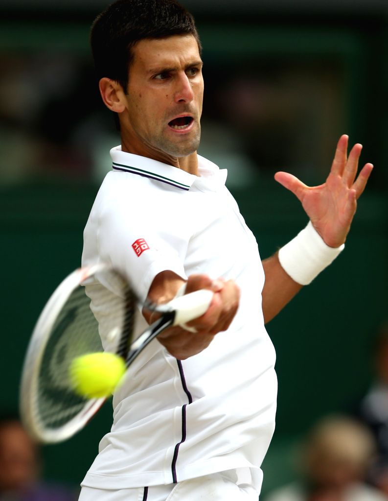 Serbia's Novak Djokovic hits a return during the men's singles final against Switzerland's Roger Federer at the 2014 Wimbledon Championships in Wimbledon, southeast ..