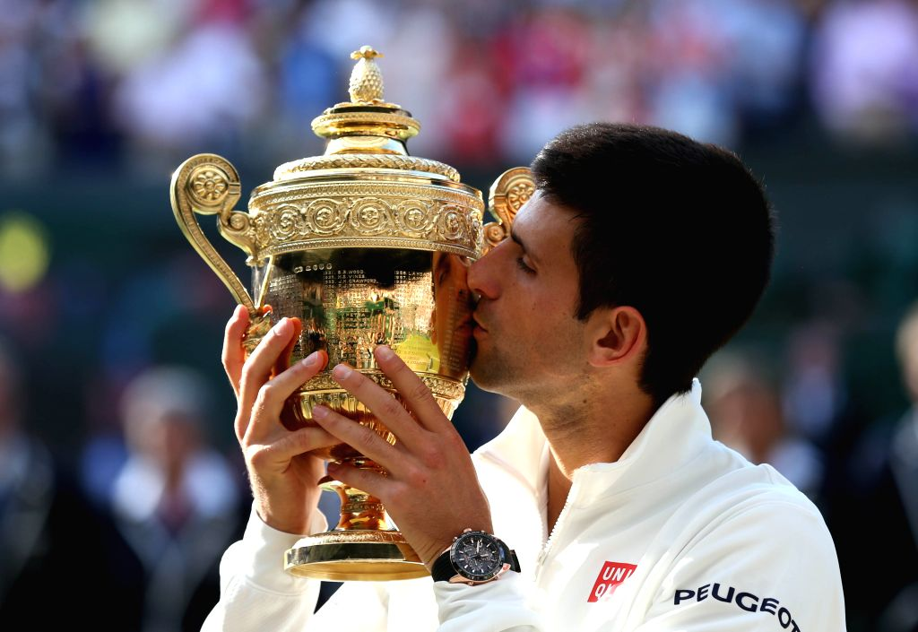 Serbia's Novak Djokovic kisses the trophy after winning the men's singles final against Switzerland's Roger Federer at the 2014 Wimbledon Championships in Wimbledon, .
