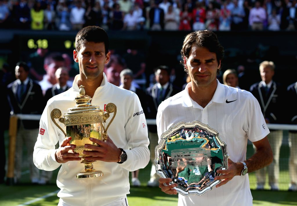 Serbia's Novak Djokovic (L) holds the winner's trophy after defeating Switzerland's Roger Federer (R), holding the runner-up's trophy, in their men's singles final at