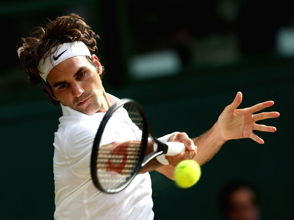 Switzerland's Roger Federer hits a return during the men's singles final against Serbia's Novak Djokovic at the 2014 Wimbledon Championships in Wimbledon, southeast ..