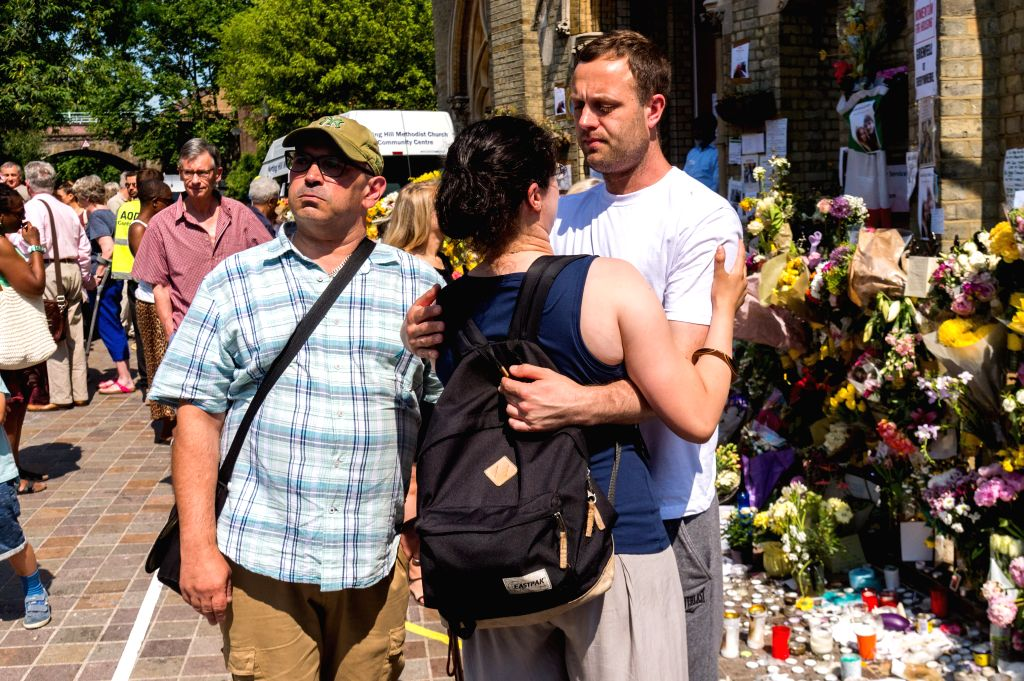 LONDON, June 19, 2017 - People comfort each other after observing a minute silence outside Notting Hill Methodist Church for the victims of the Grenfell Tower Fire in London, Britain on June 19, ...