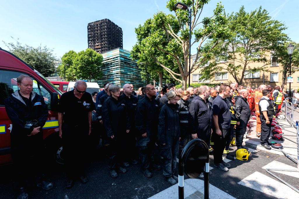 LONDON, June 19, 2017 - Representatives of the London Fire Brigade and emergency services observe a minute silence outside Notting Hill Methodist Church for the victims of the Grenfell Tower Fire in ...