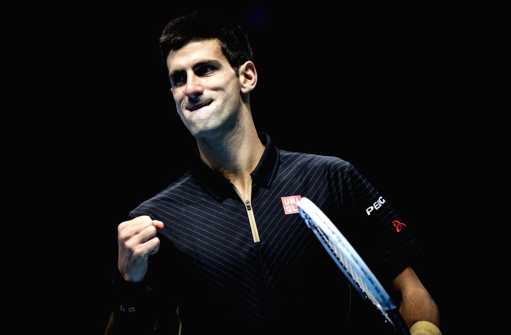 Novak Djokovic of Serbia celebrates scoring during the ATP World Tour Finals Group match against Stan Wawrinka of Switzerland in London, Britain, on Nov. 12, 2014. Djokovic won 2-0. ...