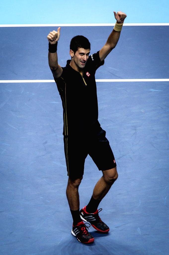 Novak Djokovic of Serbia celebrates after the ATP World Tour Finals Group match against Stan Wawrinka of Switzerland in London, Britain, on Nov. 12, 2014. Djokovic won 2-0. (Xinhua/Tang ...