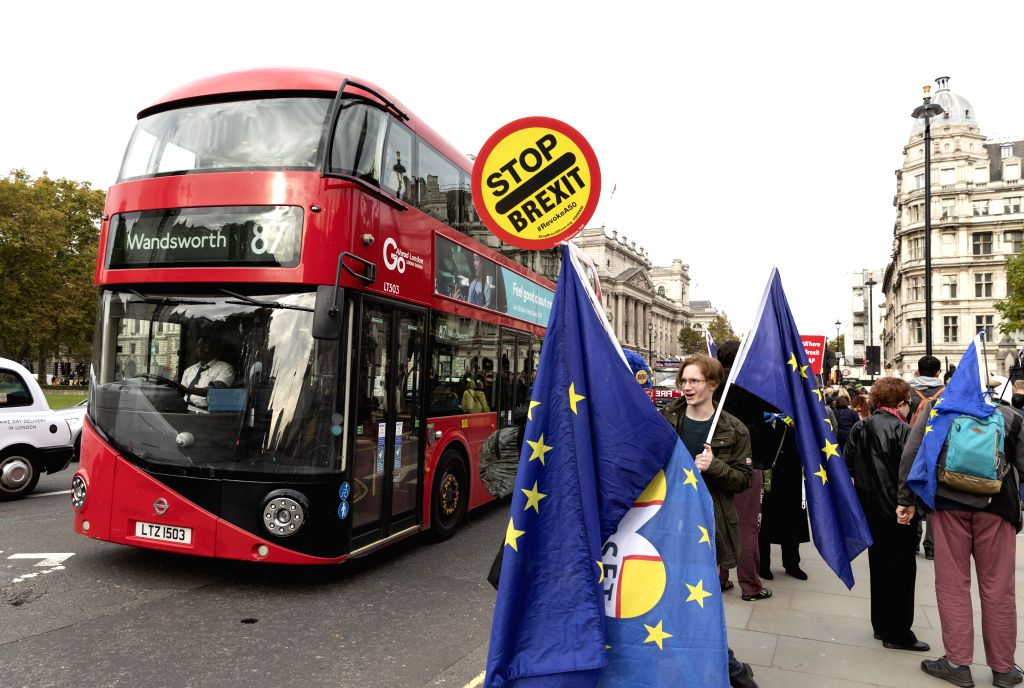 LONDON, Oct. 28, 2019 - A bus passes by anti-Brexit protesters outside the Houses of Parliament in London, Britain, on Oct. 28, 2019. The British House of Commons on Monday voted against a government ...