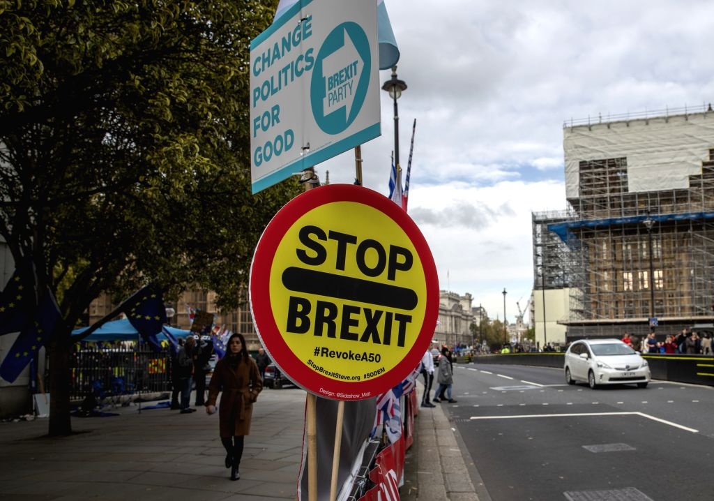 LONDON, Oct. 28, 2019 - Photo taken on Oct. 28, 2019 shows two placards with Brexit and anti-Brexit slogans outside the Houses of Parliament in London, Britain. The British House of Commons on Monday ...