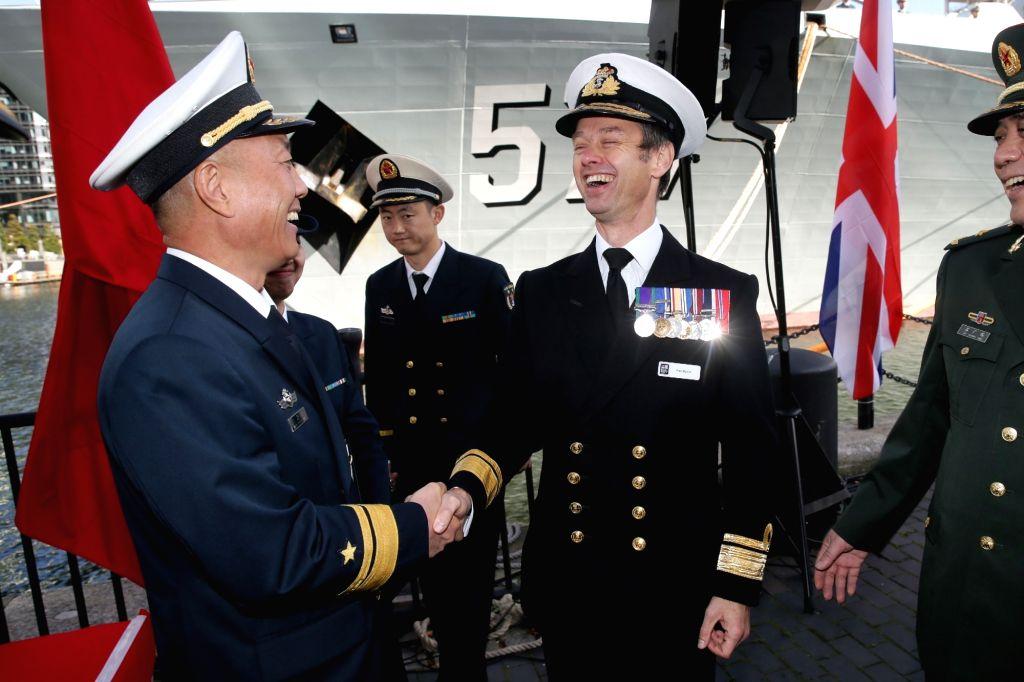 LONDON, Oct. 4, 2017 - China's 26th naval escort fleet commander Wang Zhongcai (L, front) shakes hands with British Rear Admiral Alex Burton during the welcoming ceremony of China's 26th naval escort ...