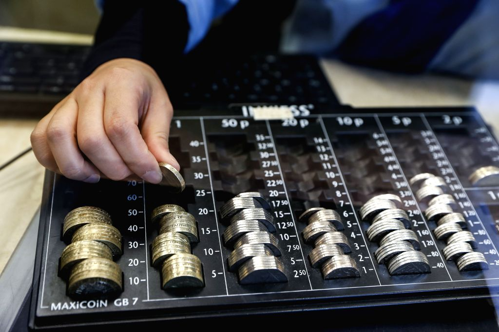 LONDON, Oct. 8, 2016 - A cashier counts pound coins in a money change bureau in central London, Britain, on Oct. 8, 2016. The Bank of England (BOE) Friday asked the Bank for International Settlements ...