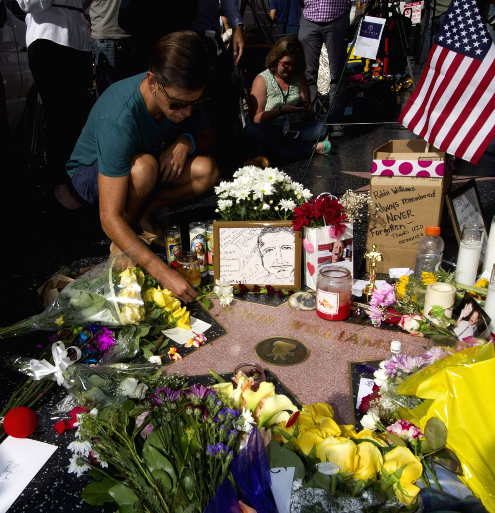 A man lays flowers at Robin Williams' star on the Hollywood Walk of Fame in Hollywood, California, the United States, Aug. 12, 2014. U.S. Oscar-winning comedian