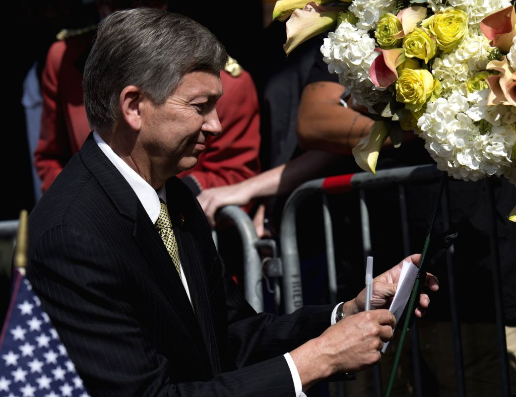 Leron Gubler, president and CEO of the Hollywood Chamber of Commerce, writes a condolence card at Robin Williams' star on the Hollywood Walk of Fame in ...