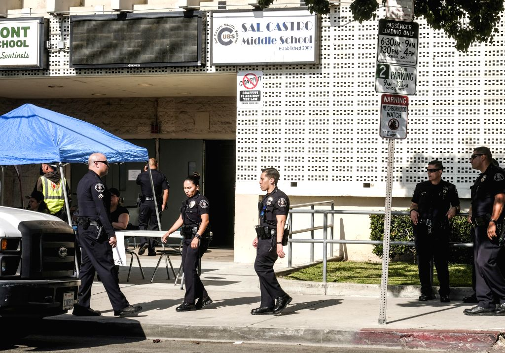 LOS ANGELES, Feb. 1, 2018 - Police officers stand guard outside Salvador Castro Middle School in Los Angeles, the United States, Feb. 1, 2018. Five people were injured, including two students shot, ...