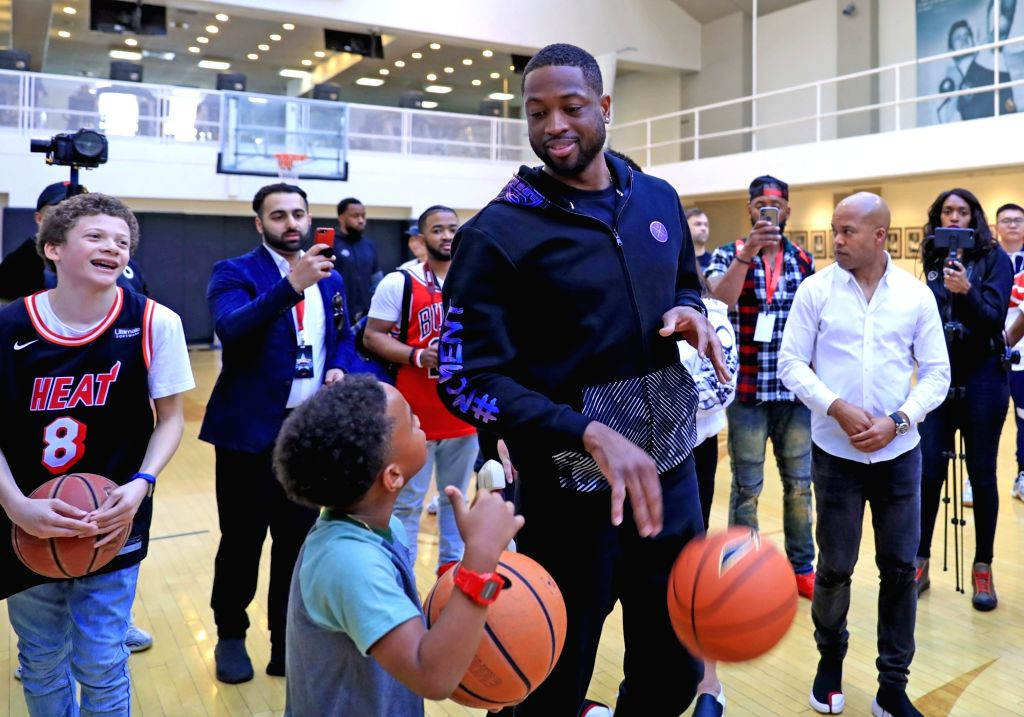 LOS ANGELES, Feb. 18, 2018 (Xinhua) -- Miami Heat player Dwyane Wade (R, front) talks with a boy during an interactive event with local children in Los Angeles, the United States, Feb. 17, 2018. Dwyane Wade coached children to learn shooting on Satur