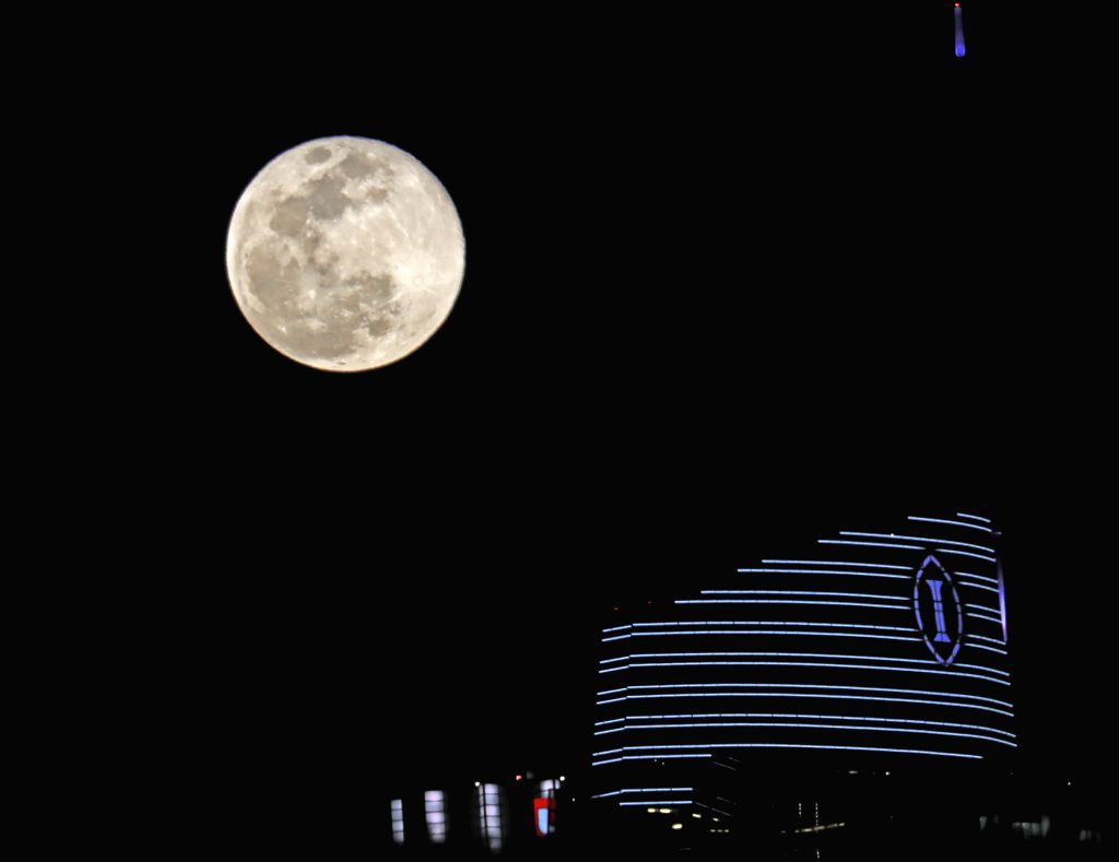 LOS ANGELES, Feb. 20, 2019 - Photo taken on Feb. 19, 2019 shows a full moon above the Wilshire Grand Center, a skyscraper in downtown Los Angeles, the United States.