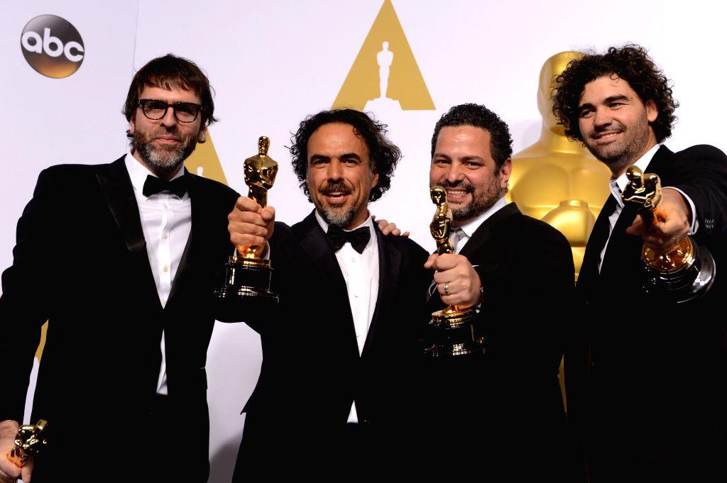 Alejandro G. Inarritu (2nd L), Nicolas Giacobone (1st L), Alexander Dinelaris (2nd R), and Armando Bo pose after winning the Best Original Screenplay award for ...