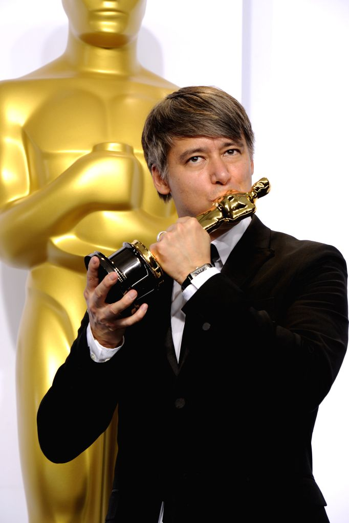"""Editor Tom Cross poses after winning the Best Film Editing award for """"Whiplash"""" during the 87th Academy Awards at the Dolby Theater in Los Angeles, ..."""