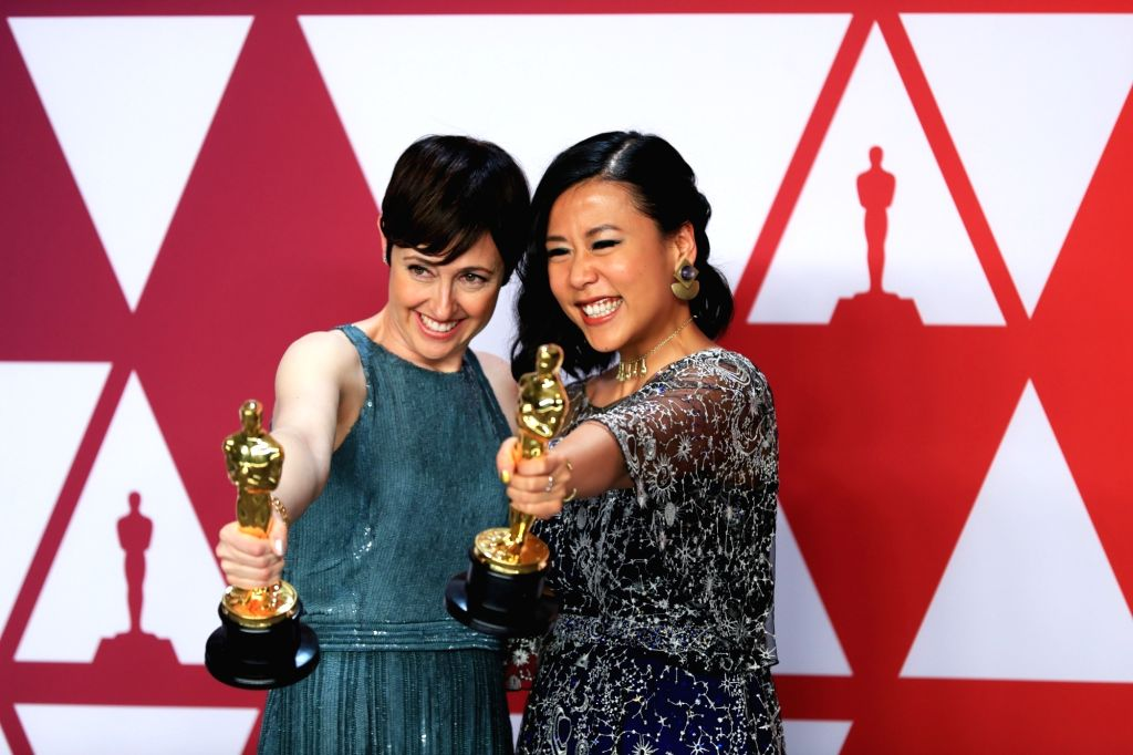 "LOS ANGELES, Feb. 25, 2019 - Becky Neiman-Cobb (L) and Domee Shi pose for photos after winning the Best Animated Short Film award for ""Bao"" in the press room during the 91st Academy Awards ..."