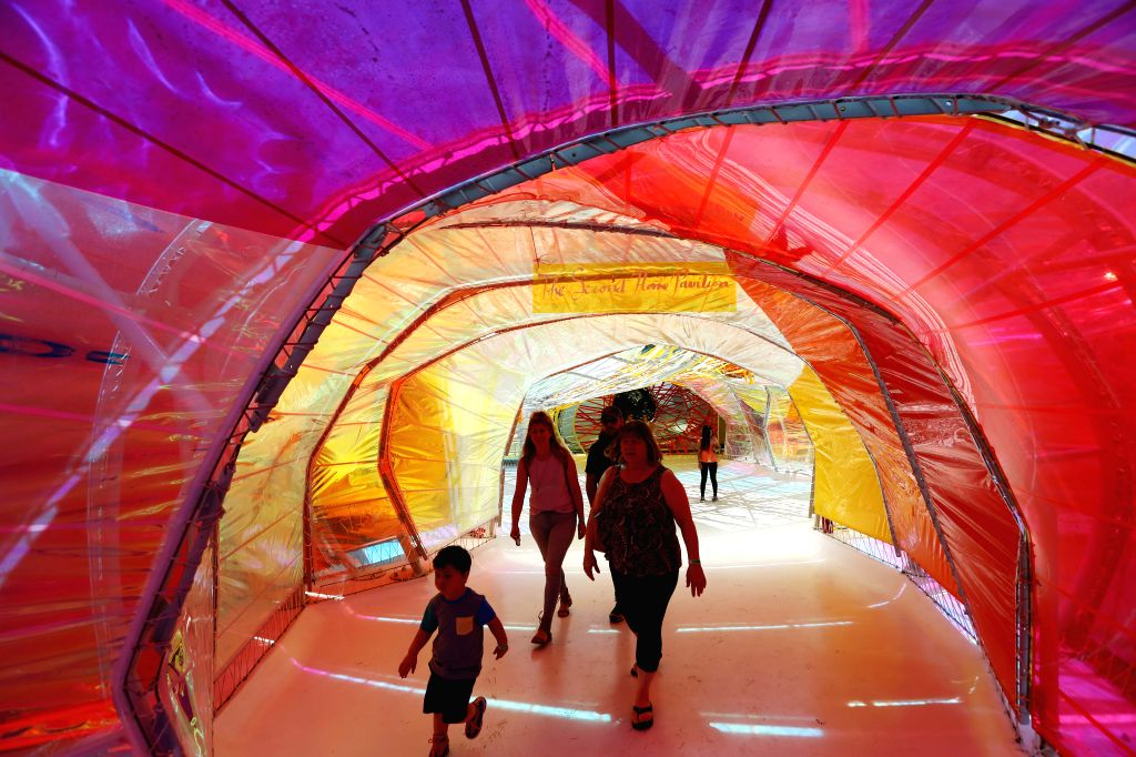 LOS ANGELES, July 17, 2019 - Tourists walk in the Serpentine Pavilion at La Brea Tar Pits in Los Angeles, the United States, July 16, 2019. The Serpentine Pavilion, rainbow tunnels of immersive, ...