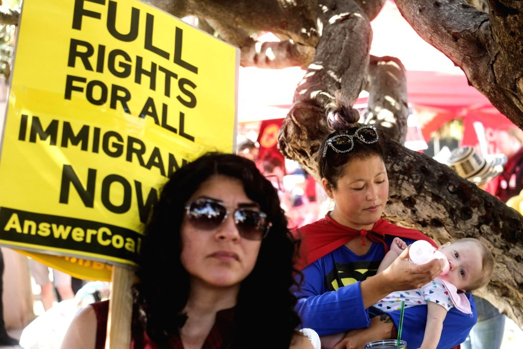 "LOS ANGELES, July 22, 2018 - A woman dressed as Superwoman feeds her baby during a ""Families Belong Together"" march in Los Angeles, the United States, on July 21, 2018. Thousands of ..."