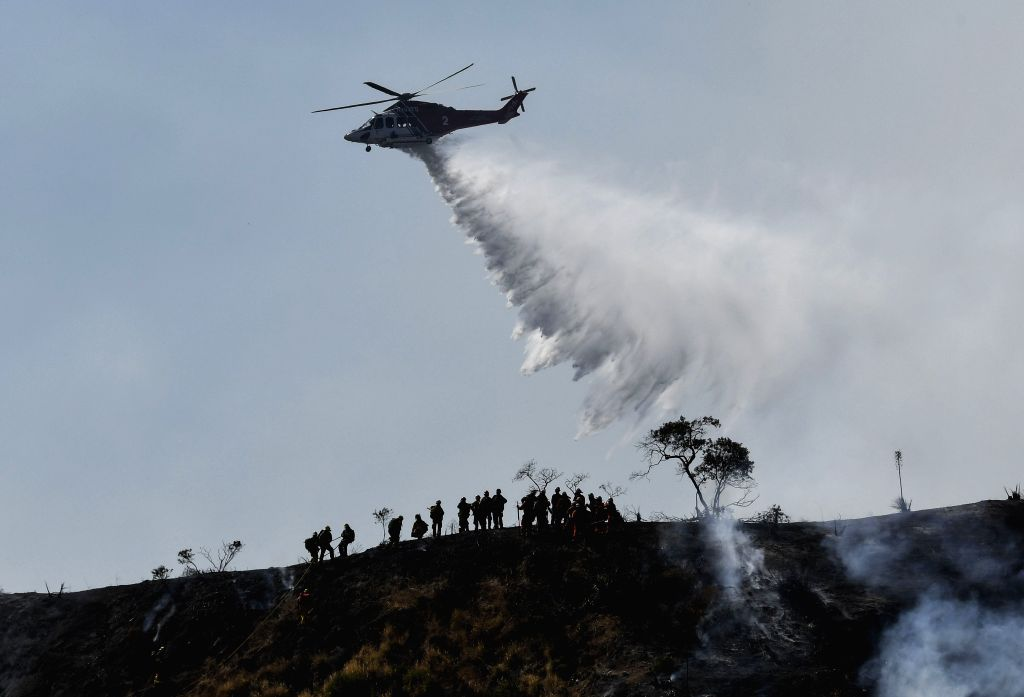 LOS ANGELES, June 29, 2017 - A helicopter tries to extinguish a wildfire in Burbank, California, the United States, June 28, 2017. A wildfire broke out on a hillside in Burbank, prompting evacuations ...