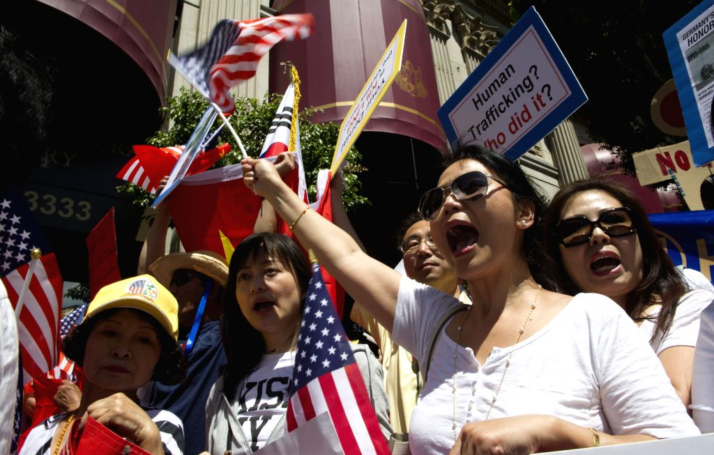 Chinese American and Korean American protesters hold signs and shout slogans during a protest outside a hotel where Japanese Prime Minister Shinzo Abe delivers a ... - Shinzo Abe