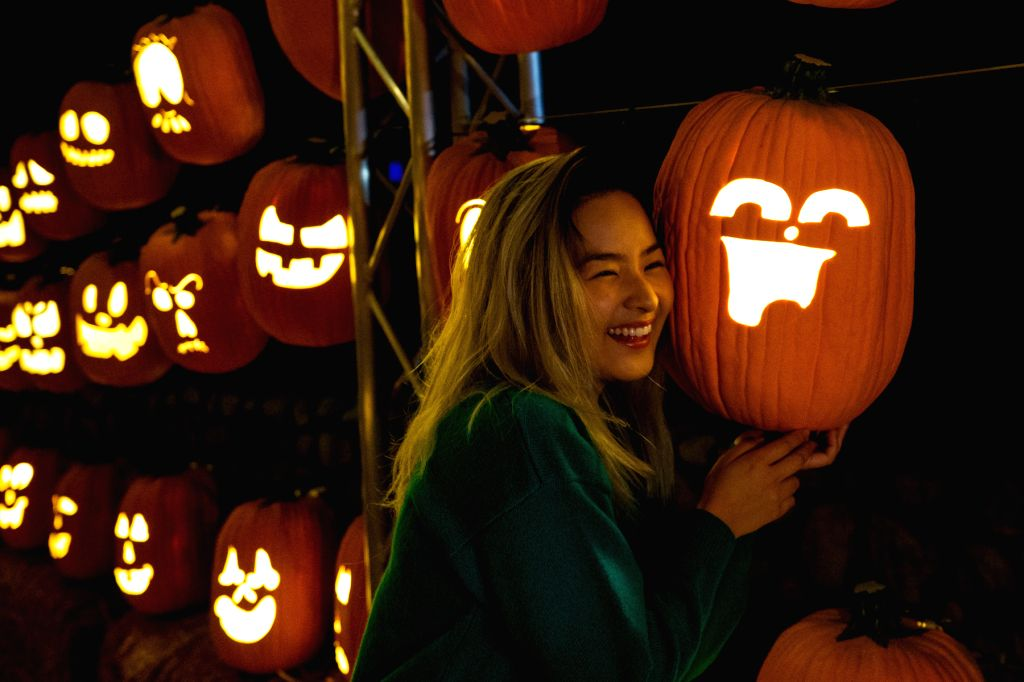 """LOS ANGELES, Oct. 15, 2019 - A visitor poses for photos with a decorated pumpkin at """"Pumpkin Night"""" in Los Angeles, the United States, on Oct. 14, 2019."""