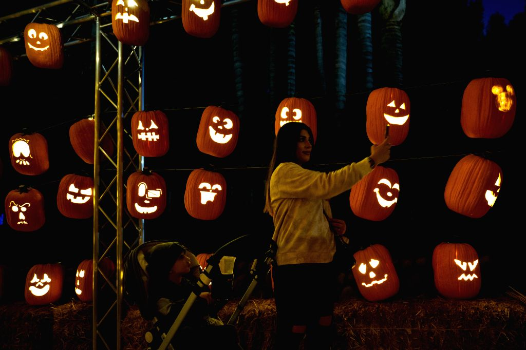"""LOS ANGELES, Oct. 15, 2019 - A visitor takes selfies at """"Pumpkin Night"""" in Los Angeles, the United States, on Oct. 14, 2019."""