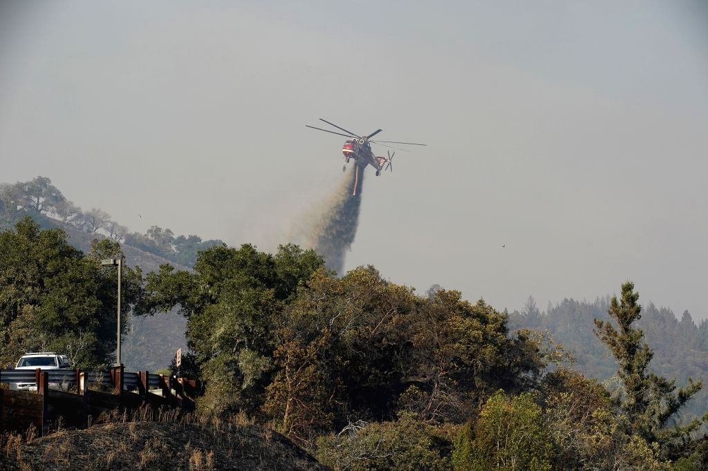 LOS ANGELES, Oct. 25, 2019 - A helicopter tries to extinguish a fire in Sonoma County, the U.S. state of California, Oct. 24, 2019. Fast-growing wild fires throughout California on Thursday burned ...