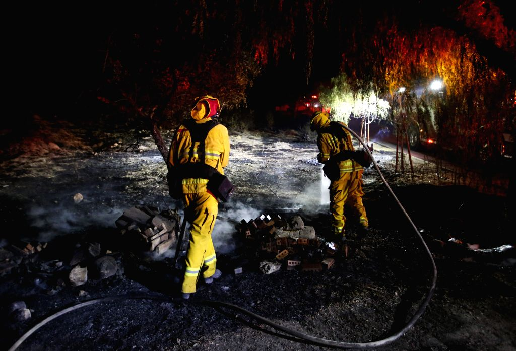 LOS ANGELES, Oct. 25, 2019 (Xinhua) -- Firefighters work at a fire spot in Santa Clarita, the U.S. state of California, Oct. 24, 2019. Fast-growing wild fires throughout California on Thursday burned down dozens of buildings, forcing tens of thousand