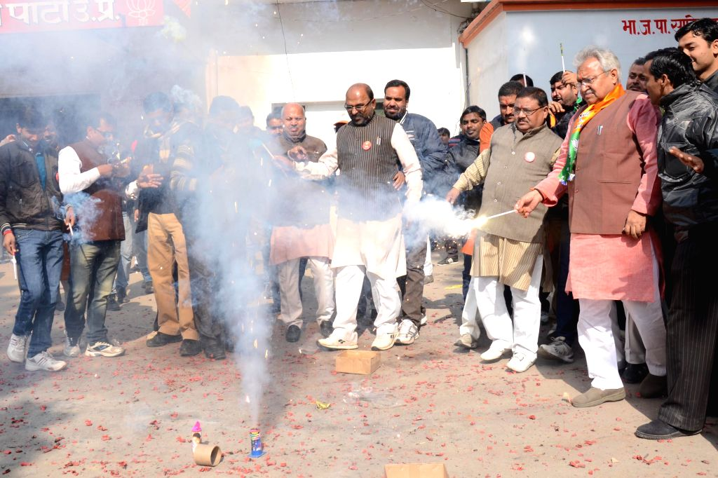 BJP workers celebrate party's performance in Jharkhand and Jammu and Kashmir assembly polls in Lucknow on Dec 23, 2014.