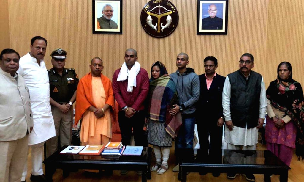 Lucknow: Family members of slain Uttar Pradesh (UP) Police Inspector Subodh Kumar Singh, who was killed in Bulandshahr mob violence, meet UP Chief Minister Yogi Adityanath at his residence in Lucknow, on Dec 6, 2018. (Photo: IANS) - Yogi Adityanath