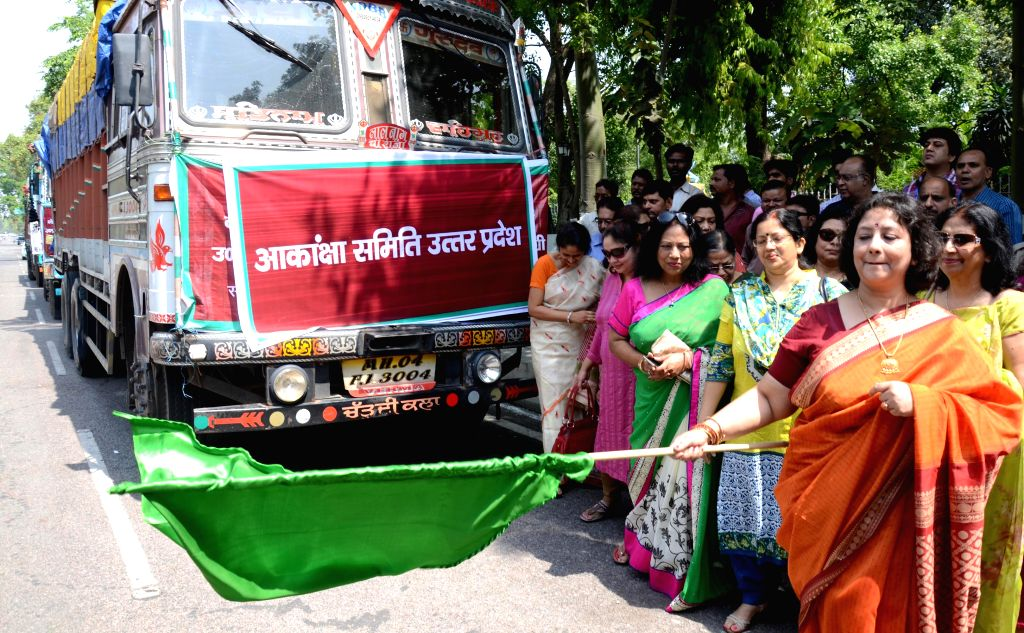 The president of Akanksha Samiti Surabhi Ranjan flags-off three trucks carrying relief materials for earthquake victims in Nepal from Lucknow on April 29, 2015.